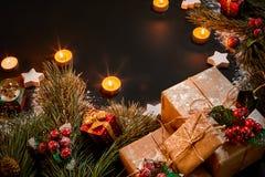 Julgåvor, julträdet, stearinljus, den kulöra dekoren, stjärnor, klumpa ihop sig på svart bakgrund Arkivbilder