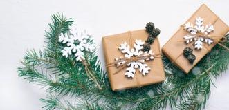 Julgåvor med granfilialer på vit bakgrund, begrepp för vinterferier, långt format arkivfoto