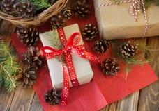 Julgåvor och kottar och på en trätabell fotografering för bildbyråer