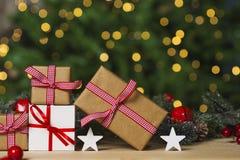 Julgåvor och prydnad på tabellen, ljusbokehbakgrund arkivfoto