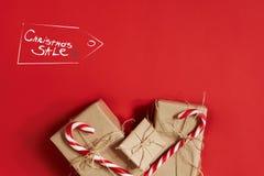 Julgåvor på varm röd bakgrund Tema för jul och för nytt år Ställe för din text, önska, logo Åtlöje upp Arkivfoto