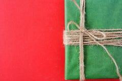 Julgåvor packade in i Kraft papper på en röd bakgrund royaltyfria bilder