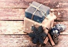 Julgåvor som dekoreras med linnekabel, kanel, sörjer kottar, julgarnering tappning tonad bild royaltyfri foto