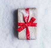Julgåvor som slås in i hantverkpapper med det röda bandet på snöbakgrund, bästa sikt med kopieringsutrymme för din hälsa design arkivbild