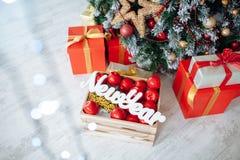 Julgåvor som slås in i klassiskt rött papper och träbokstäver nytt år, bakgrund med xmas-trädet kopiera avstånd royaltyfria foton