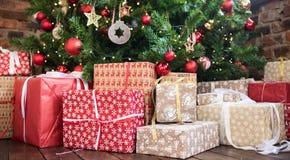 Julgåvor under den röda och träleksakertegelstenväggen för julgran Nytt år 2019 royaltyfri bild