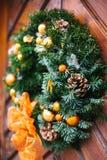 Julgarnering av dörren med en härlig traditionell krans Fira jul som dekorerar huset Royaltyfria Foton