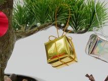 Julgarnering eller prydnadhängning på konstgjort bonsaiträd komponerade av guld- och silvergåvaasken som isolerades på vit bakgru Royaltyfri Foto