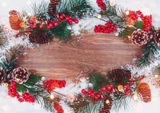 Julgarnering, filial av granträdet med kottar och snö på träbakgrund Royaltyfria Foton