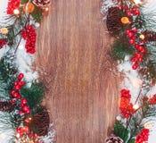Julgarnering, filial av granträdet med kottar och snö på träbakgrund Arkivbild