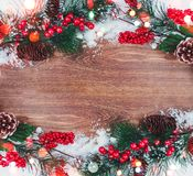 Julgarnering, filial av granträdet med kottar och snö på träbakgrund Arkivfoto