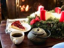 Julgarnering framme av brandstället med krikonet Plum Tart Cake och kaffe royaltyfria foton