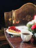 Julgarnering framme av brandstället med krikonet Plum Tart Cake och kaffe arkivfoto
