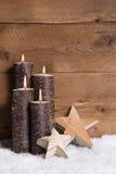 Julgarnering: Fyra brännande stearinljus, stjärnor och snö på wo Royaltyfria Bilder