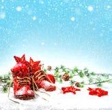 Julgarnering med antikviteten behandla som ett barn skor fallande snöeffekt royaltyfri foto