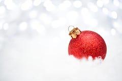 Julgarnering med den röda bollen i snön på den suddiga bakgrunden med ferieljus greeting lyckligt nytt år för 2007 kort Fotografering för Bildbyråer