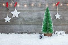 Julgarnering med det liten granträdet, pulkan, stjärnor och holi royaltyfri bild