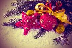 Julgarnering med granfilialen och den röda prydnaden Arkivbilder