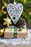 Julgarnering med granträdet, gåvaasken, hjärta för vit jul och sörjer kottar på gammal träbakgrund Arkivbild