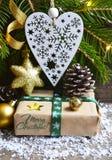 Julgarnering med granträdet, gåvaasken, hjärta för vit jul och sörjer kottar på gammal träbakgrund Royaltyfri Bild