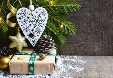 Julgarnering med granträdet, gåvaasken, hjärta för vit jul och sörjer kottar på gammal träbakgrund Royaltyfria Bilder