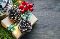 Julgarnering med granträdet, gåvaasken, röda bär, girlandljus och sörjer kottar på gammal träbakgrund Royaltyfria Foton