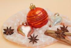 Julgarnering med kanelbruna pinnar, stjärnaanis och julbollar Arkivfoto