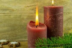 Julgarnering med kanelbruna stjärnor, julbollar, stearinljus Royaltyfri Foto