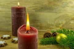 Julgarnering med kanelbruna stjärnor, julbollar, stearinljus Royaltyfria Foton