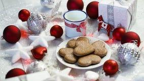 Julgarnering med röda bubblor för silvergåvor och hemlagade kakor, rött ljus och att mjölka arkivfilmer