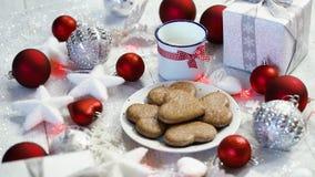 Julgarnering med röda bubblor för silvergåvor och hemlagade kakor, rött ljus och att mjölka stock video