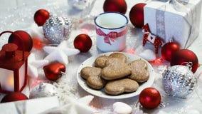 Julgarnering med röda bubblor för silvergåvor och hemlagade kakor, rött ljus och att mjölka lager videofilmer