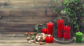 Julgarnering med röda stearinljus och kanelbruna kakor Fotografering för Bildbyråer