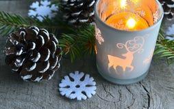 Julgarnering med sörjer kottar, stearinljuset, granträdfilial och klädde med filt snöflingor på den gamla trätabellen Arkivbilder
