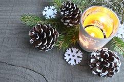 Julgarnering med sörjer kottar, stearinljuset, granträdfilial och klädde med filt snöflingor på den gamla trätabellen Royaltyfria Bilder