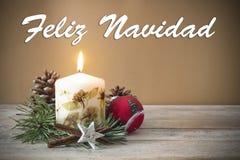 Julgarnering med stearinljuset, sörjer, struntsaken, med text i spansk `-Feliz Navidad ` i träbakgrund royaltyfria bilder