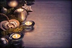 Julgarnering och stearinljus på träbräde Arkivbilder