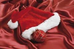 Julgarnering, röda julstruntsaker på rött tyg Royaltyfria Foton