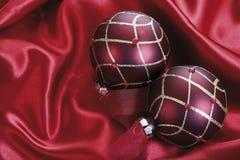 Julgarnering, röda julstruntsaker på rött tyg Arkivfoto