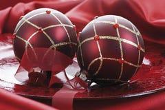 Julgarnering, röda julstruntsaker på rött tyg Arkivbild