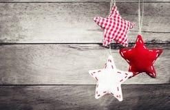 Julgarnering som hänger över lantlig träbakgrund. Vint Royaltyfri Fotografi