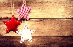 Julgarnering som hänger över lantlig träbakgrund. Vint Arkivfoto
