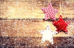 Julgarnering som hänger över lantlig träbakgrund. Vint Fotografering för Bildbyråer