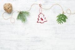 Julgirland av barrträdfilialer & det röda julträdet mot vit träbakgrund royaltyfri bild
