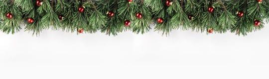 Julgirland av granfilialer med röd garnering på vit bakgrund Tema för Xmas och för lyckligt nytt år royaltyfria bilder