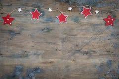 Julgirland från de röda trästjärnorna på den lantliga bakgrunden royaltyfri foto