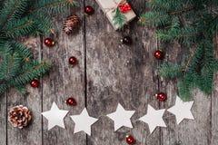 Julgirlanden av stjärnor, gåvor, sörjer kottar, röda garneringar på träbakgrund arkivbilder