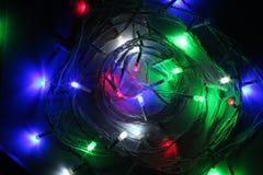 Julgirlanden med mång- kulöra kulor och ljus, jul, färgade små ljus stänger sig upp royaltyfria foton
