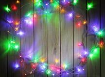 Julgirlander av lampor på en träbakgrund Royaltyfri Foto