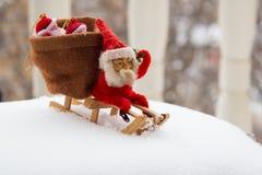 Julgnomen sitter på träsläden med påsen av gåvor bak honom Arkivfoto